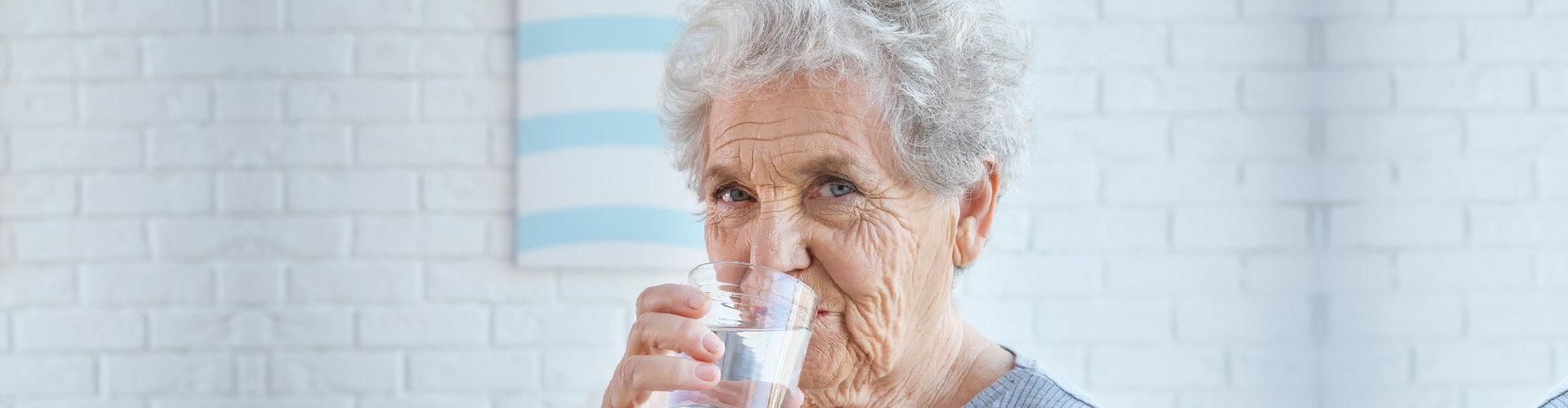 an elderly woman drinking